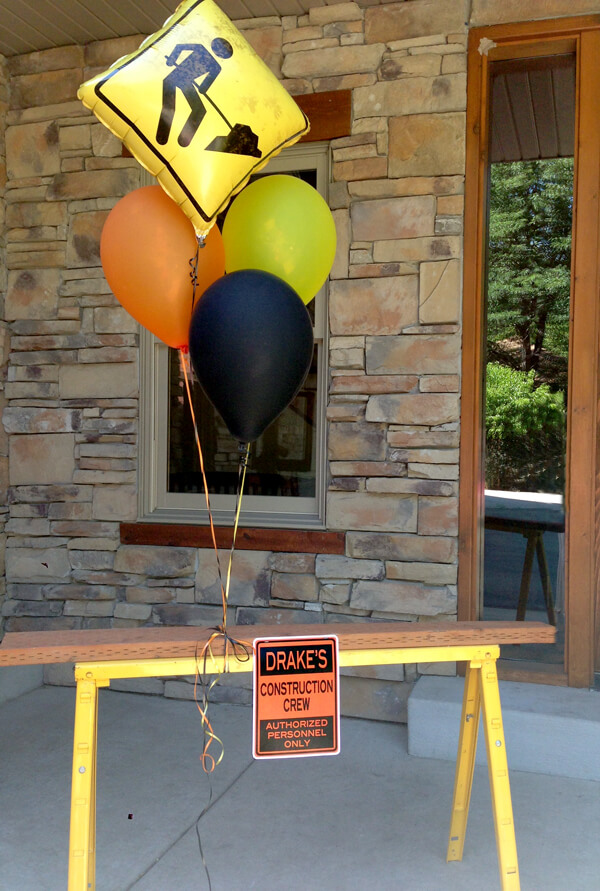 Construction 3rd birthday party blast | Halfpint Party - saw horse with balloons and a sign to welcome guests