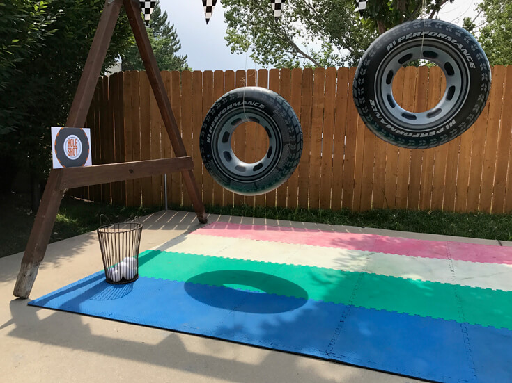 """The """"Hole Shot"""" activity was a tough one for the 5 year old crowd. Toss a ball through the open hole of huge inflatable tires. For older kids have the tires spin slowly for an added challenge. Monster truck activity ideas-halfpintpartydesign.com-boy party theme"""