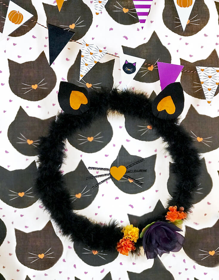 """This furry kitty wreath is such a great backdrop. It's so easy to make and everyone loved it! """"Black Cat Halloween Party Reveal"""" on Halfpint Design - Halloween party ideas, kitty cat party, kids party, cat party treats"""