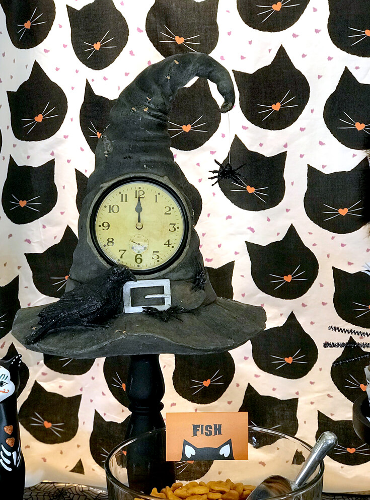 """Some witchy details included an amazing witch hat clock on a pedestal. """"Black Cat Halloween Party Reveal"""" on Halfpint Design - Halloween party ideas, kitty cat party, kids party, cat party treats"""