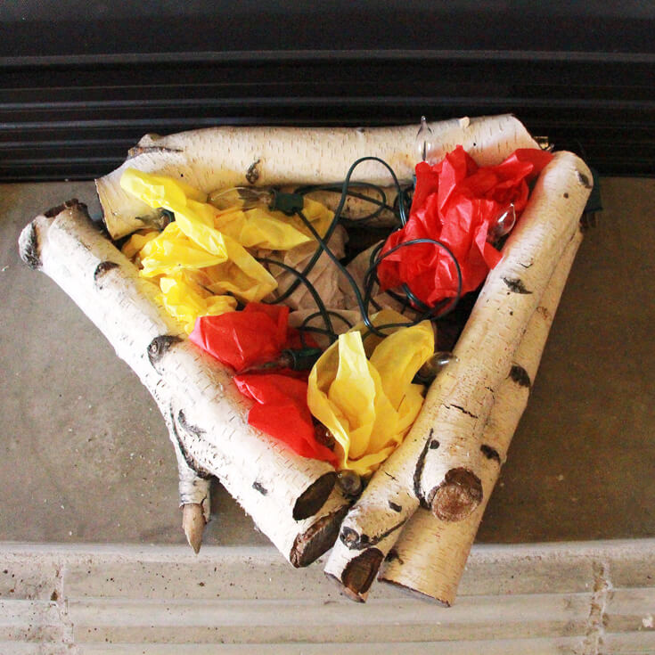 Step 3: Crumple yellow and red tissue paper to line the of the birch logs. Create an Eerie Witches' Cauldron | Halfpint Design - Halloween decorations, witch decor, faux fire, fake campfire, firelight bulbs