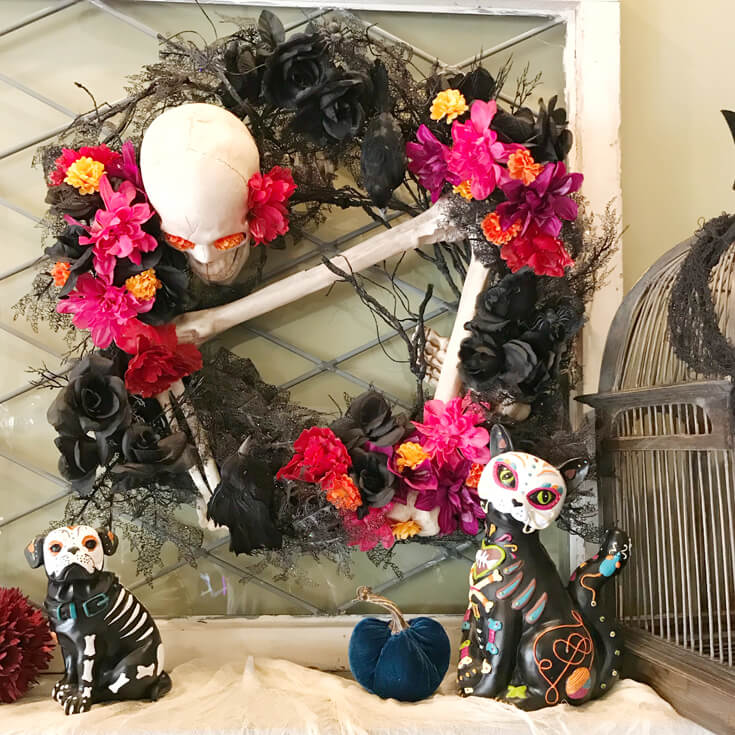 The finished Day of the Dead Wreath for a Coco viewing party! I love all the colors and how bright and cheery it has now become. The skeleton is made even less menacing with the sugar skull cat and dog figures on the mantel. Day of the Dead Holiday Wreath Transformation from Halfpint Design. Day of the Dead party, Dia de los Muertos decor, Decor DIY