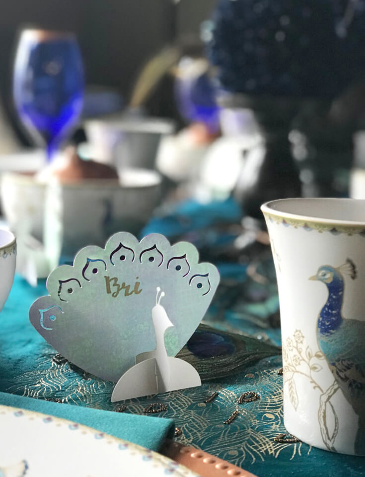 Peacock place cards in 3D with hand lettered names for a peacock Thanksgiving, Christmas, or dinner party table. See more Global Chic Holiday Tablescape ideas at Halfpint Design. Thanksgiving Tablescape, Place setting, Christmas Table, Holiday decor.