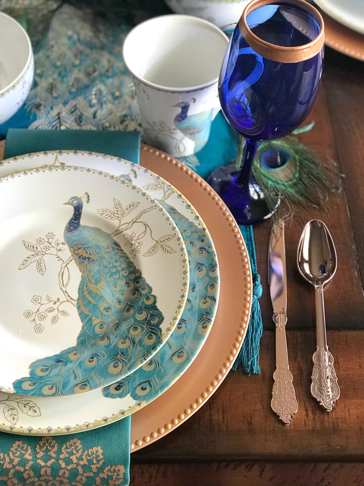 Peacock china with copper and cobalt accessories for an elegant Thanksgiving, Christmas, or dinner party table. See more Global Chic Holiday Tablescape ideas at Halfpint Design. Thanksgiving Tablescape, Place setting, Christmas Table, Holiday decor.