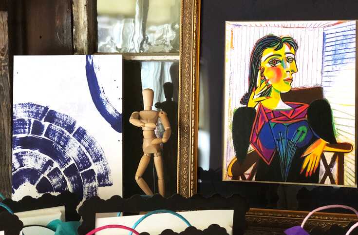 Abstract piece of art, wooden artist mannequin, and framed Picasso print as decorations for an Art birthday Party