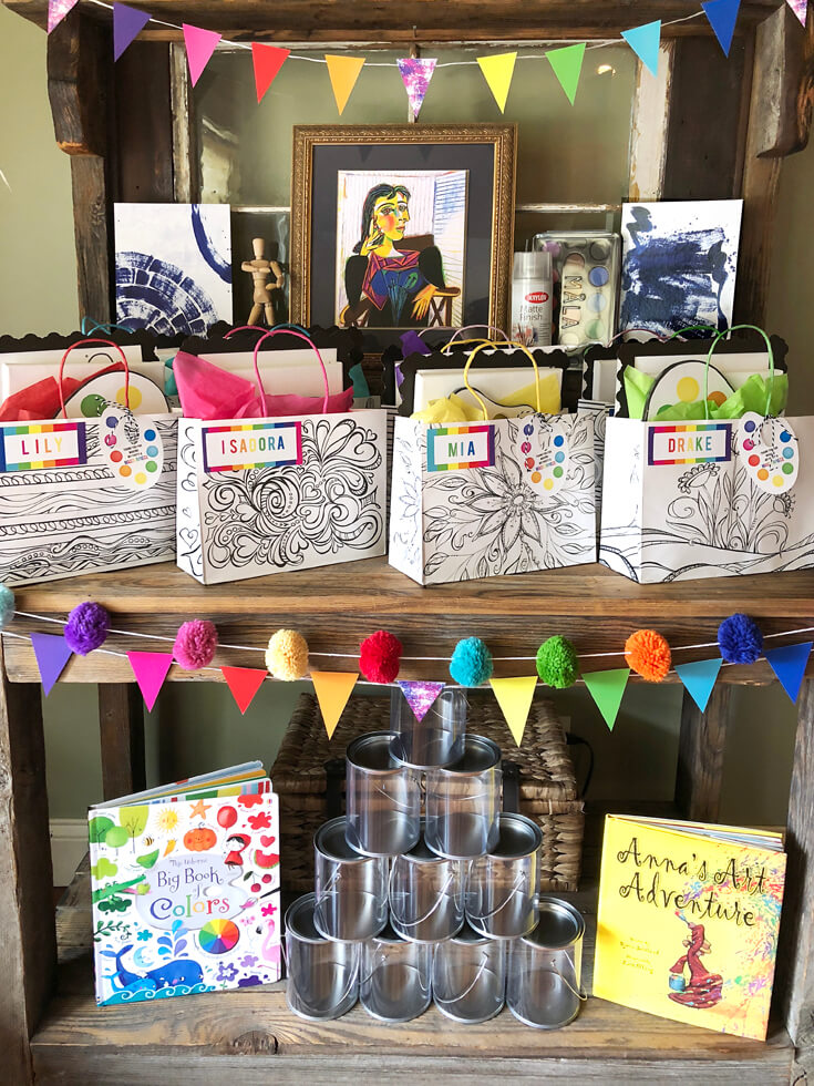 Rustic wood hutch set up as a favor table with art supplies, Black and white floral bags with rainbow name tags and a personalized paint palette tag as Art Party Favors