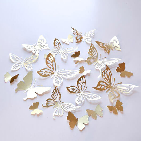 Gold and white cut butterfly decorations for an enchanted butterfly party.