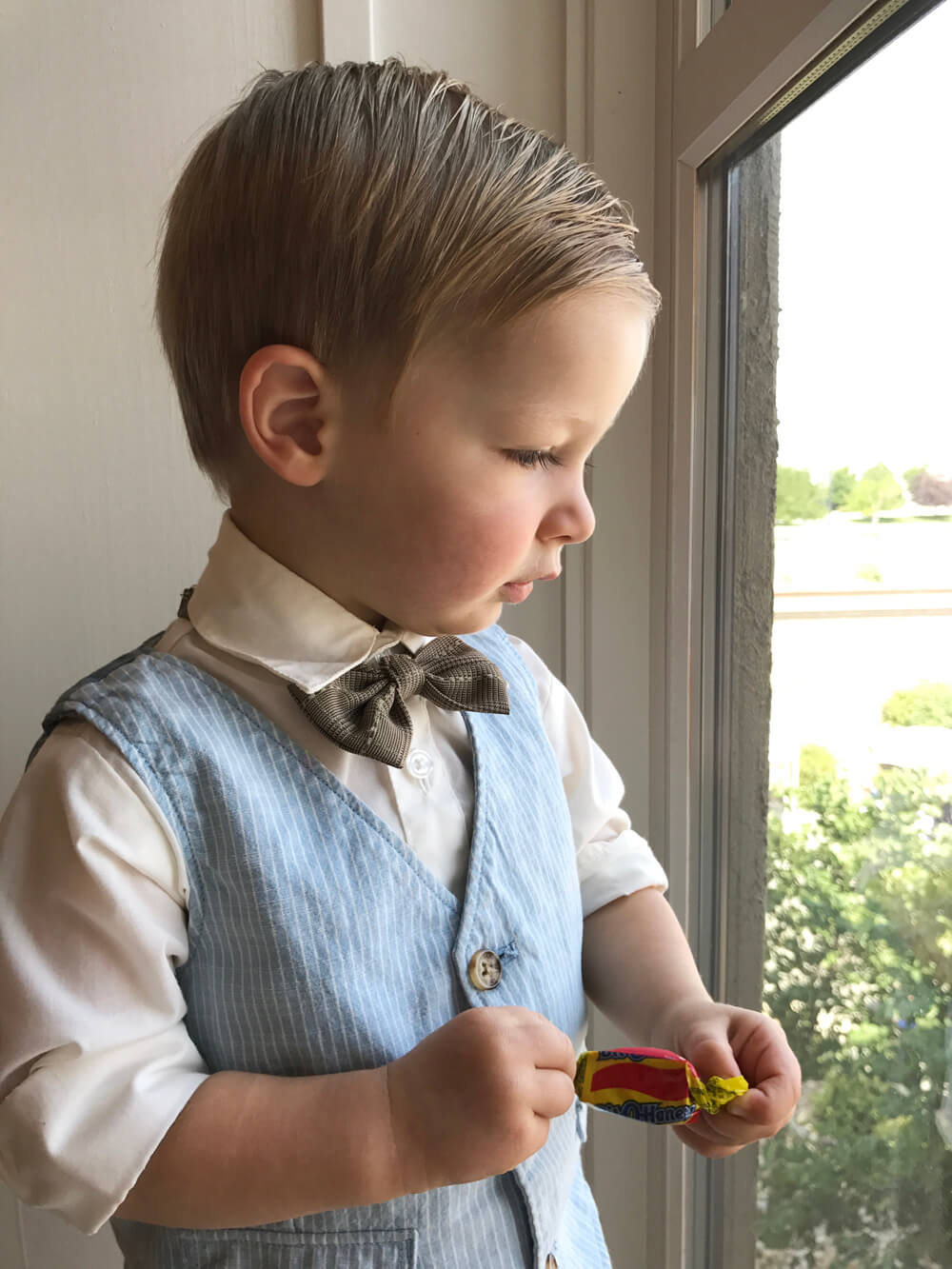 Little boy dressed up with bit o honey candy at mommy to bee baby shower