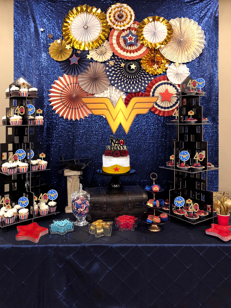 Dessert table with colorful fans and logo for a Wonder Woman party