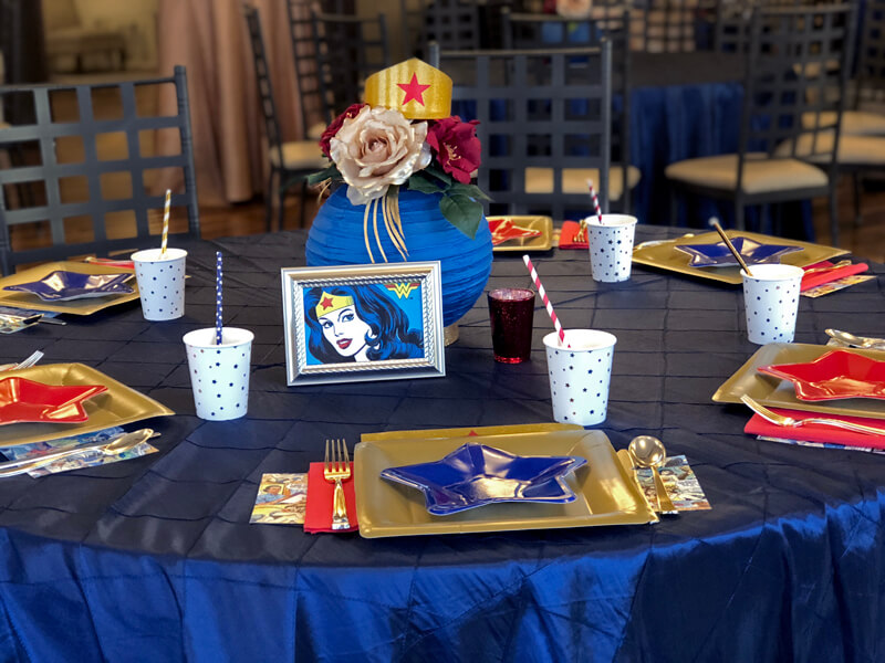 Table set with gold and star plates and floral lantern centerpiece for a Wonder Woman birthday party