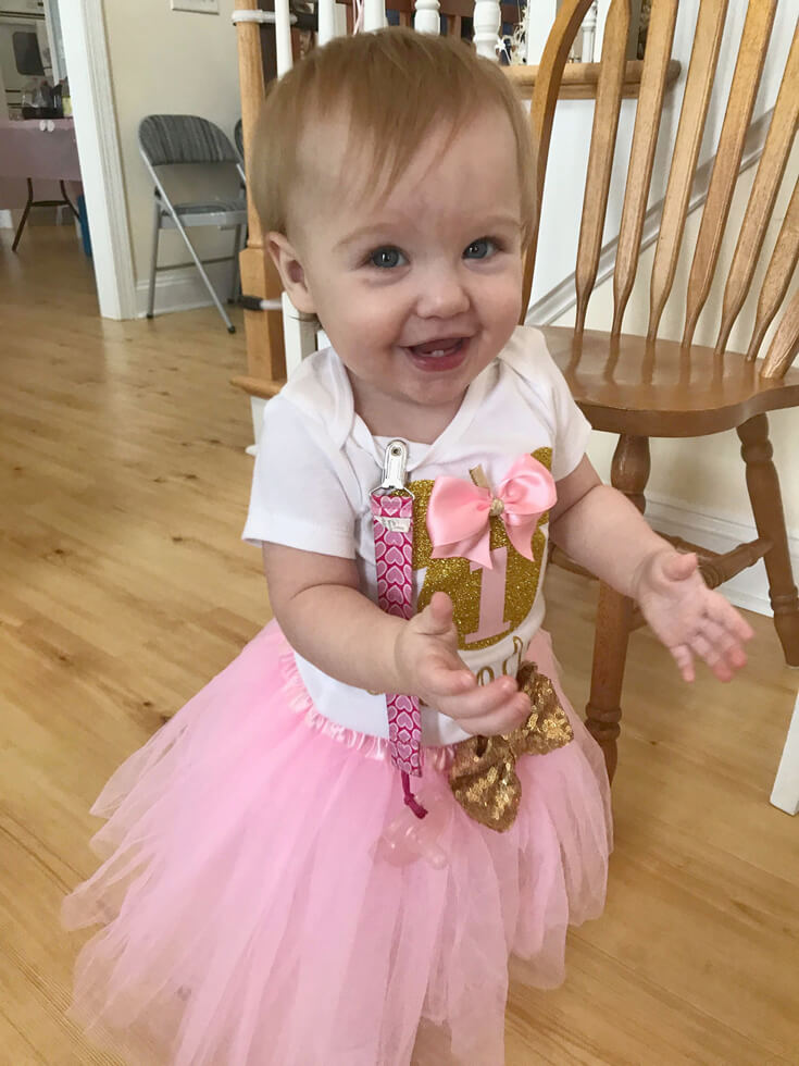 Darling birthday girl in party clothes for Minnie Mouse first birthday party