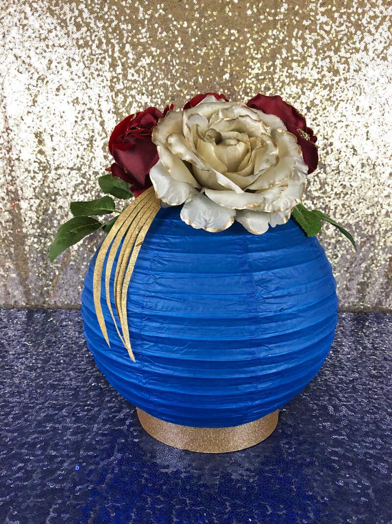 Blue paper lantern filled with silk flowers in red and gold on navy sequin table cover as a Wonder Woman themed floral lantern centerpiece.