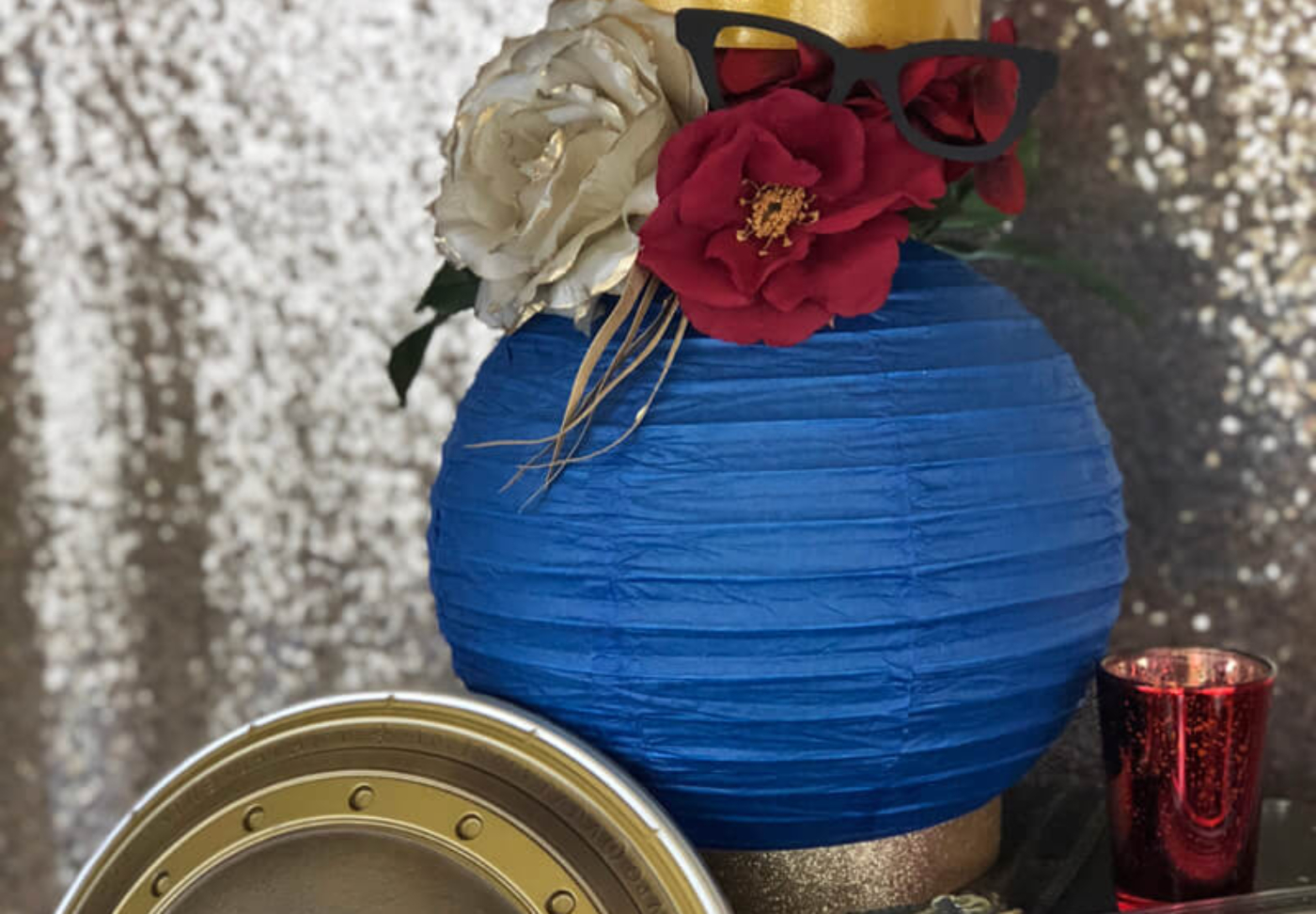 Wonder woman party display with blue paper lantern filled with flowers and topped with a crown for a floral lantern centerpiece.