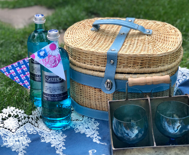 Picnic basket, blue glasses, and mineral water bottles on blanket for charming summer picnic party