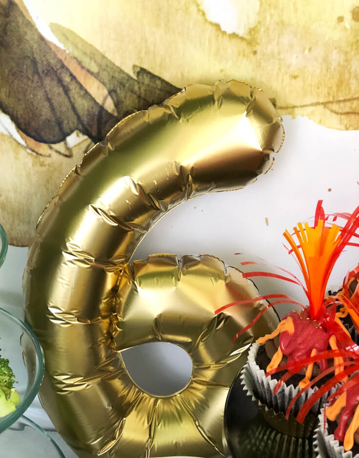 Gold number 6 balloon on dessert table for a dinosaur birthday party