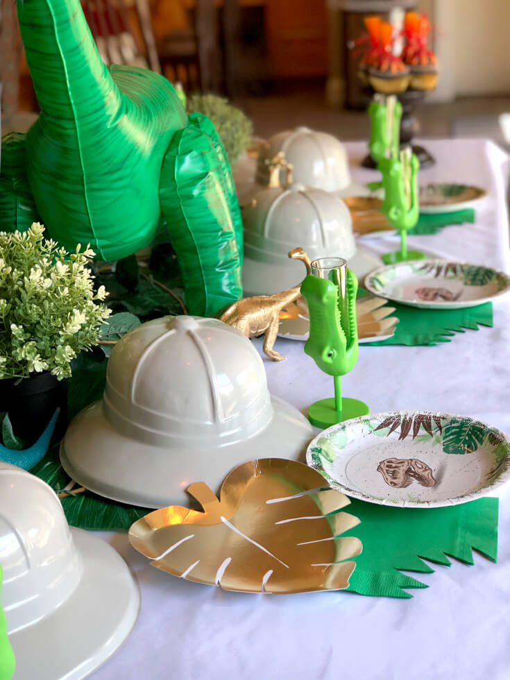Gold monstera leaf and T-rex plates, green napkin with a bite, reptile cup, and pith hat for the perfect dinosaur birthday party place setting