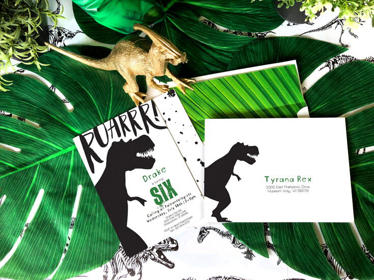 T-Rex inspired invitations with palm leaf background and personalized envelopes are a fun dinosaur birthday party idea!