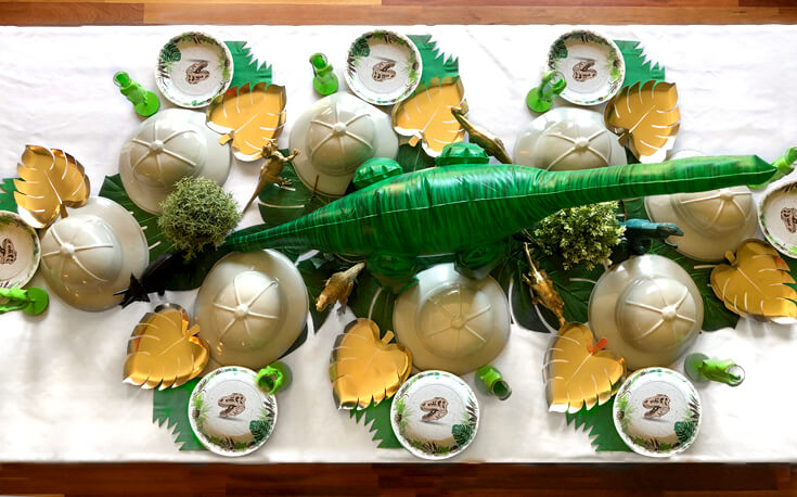 Prehistoric dino party table with pith hats, and large dino centerpiece for a dinosaur birthday party idea