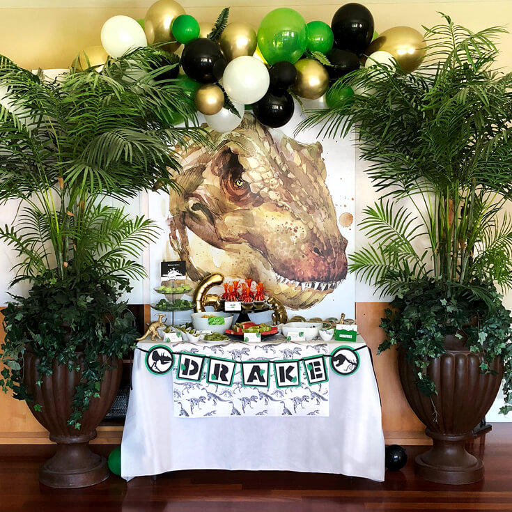 T-rex graphic backdrop, balloon garland, and potted palm trees are a fabulous dinosaur birthday party idea!