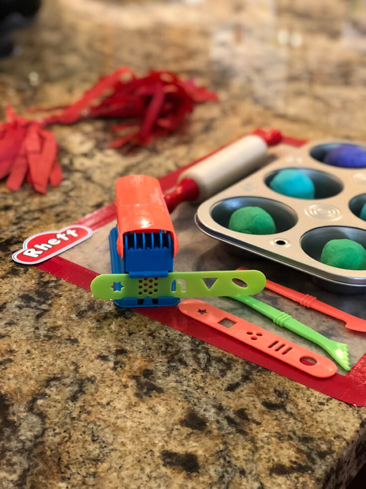 Homemade playdough in muffin tins with an extruder for a Play-doh birthday party