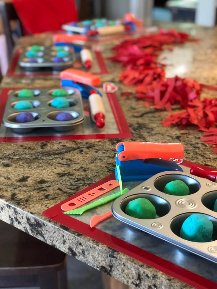 Homemade playdough in muffin tins with extruders on counter for a Play-doh birthday party