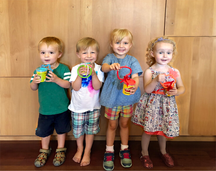 Guests showing their Play-doh party favors at a Play-doh birthday party