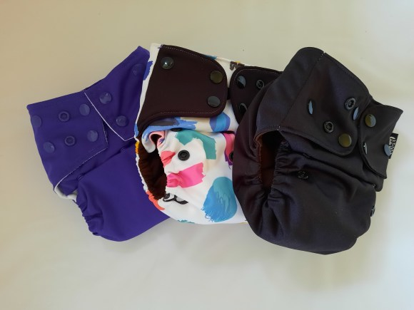 Three reusable nappies - a purple one, a patterned one and a black one.
