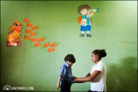 A teacher helps a boy with his belt after nap time.