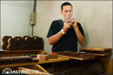 A bunchero checks quality control on one of the RoMa Craft cigars that was just rolled.