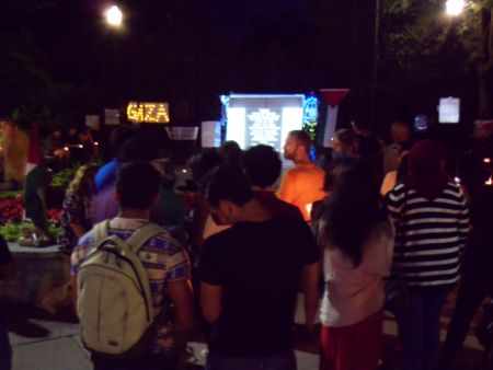 People at the vigil watch the slideshow on the screen