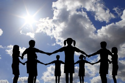 silhouettes of children standing holding hands in a circle with sunny sky and clouds in the background