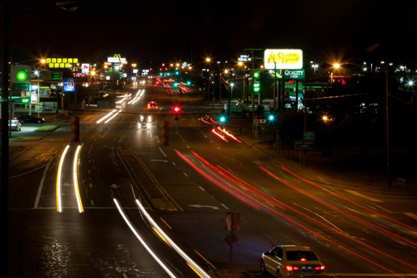time-lapse photo of traffic on the highway with illuminated signs for restaurants, service stations, shopping, and hotels