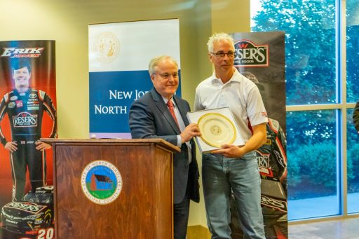 NC Secretary of Commerce Anthony M. Copeland standing aside a podium with Plant Manager Steve Snyder accepting a gift gold rimmed plate with the seal of North Carolina printed.