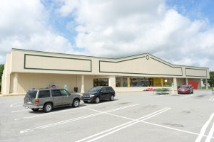 exterior photo of front of grocery store building showing cars in parking spaces and front entrances
