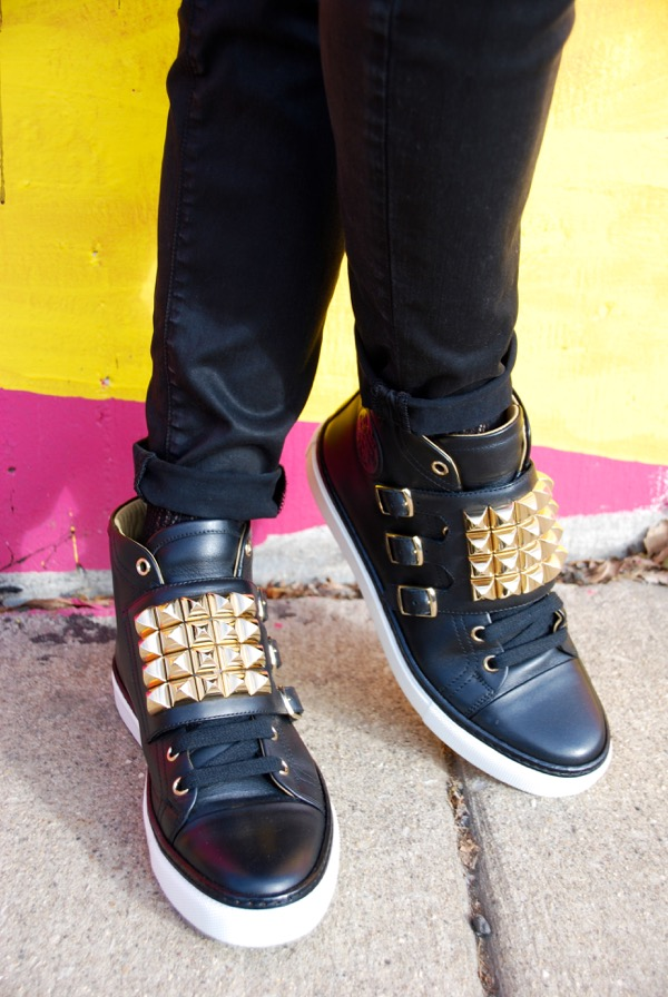 details of black sneakers with buckles and gold studs