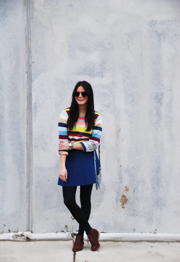 smiling in a colorful stripe gap sweater and j crew skater skirt