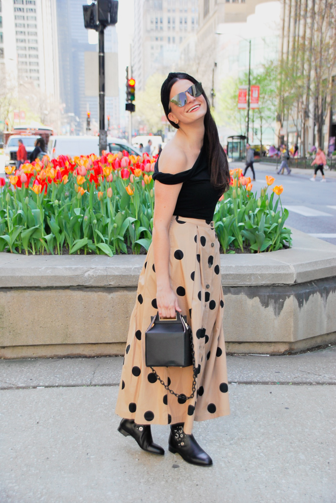 tan skirt with black polka dots, asymmetrical one shoulder black bodysuit, black booties, black knotted headband