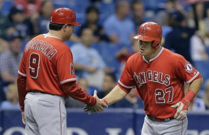 Los Angeles Angels' Mike Trout (27) shakes hands with third base coach Gary DiSarcina after hitting a home run off Tampa Bay Rays starting pitcher Alex Colome during the sixth inning of a baseball game Thursday, June 11, 2015, in St. Petersburg, Fla. (AP Photo/Chris O'Meara)