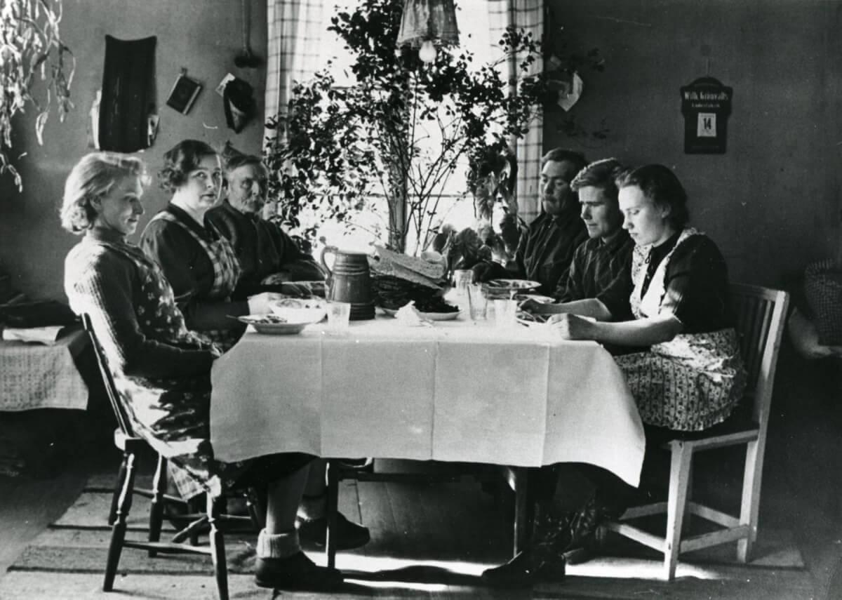 En familj sitter runt ett matbord.