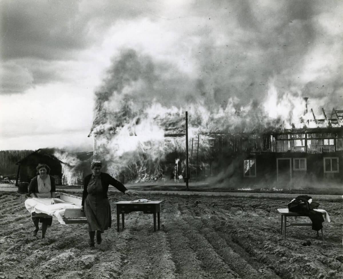 Kvinnor bär säng framför brinnande hus