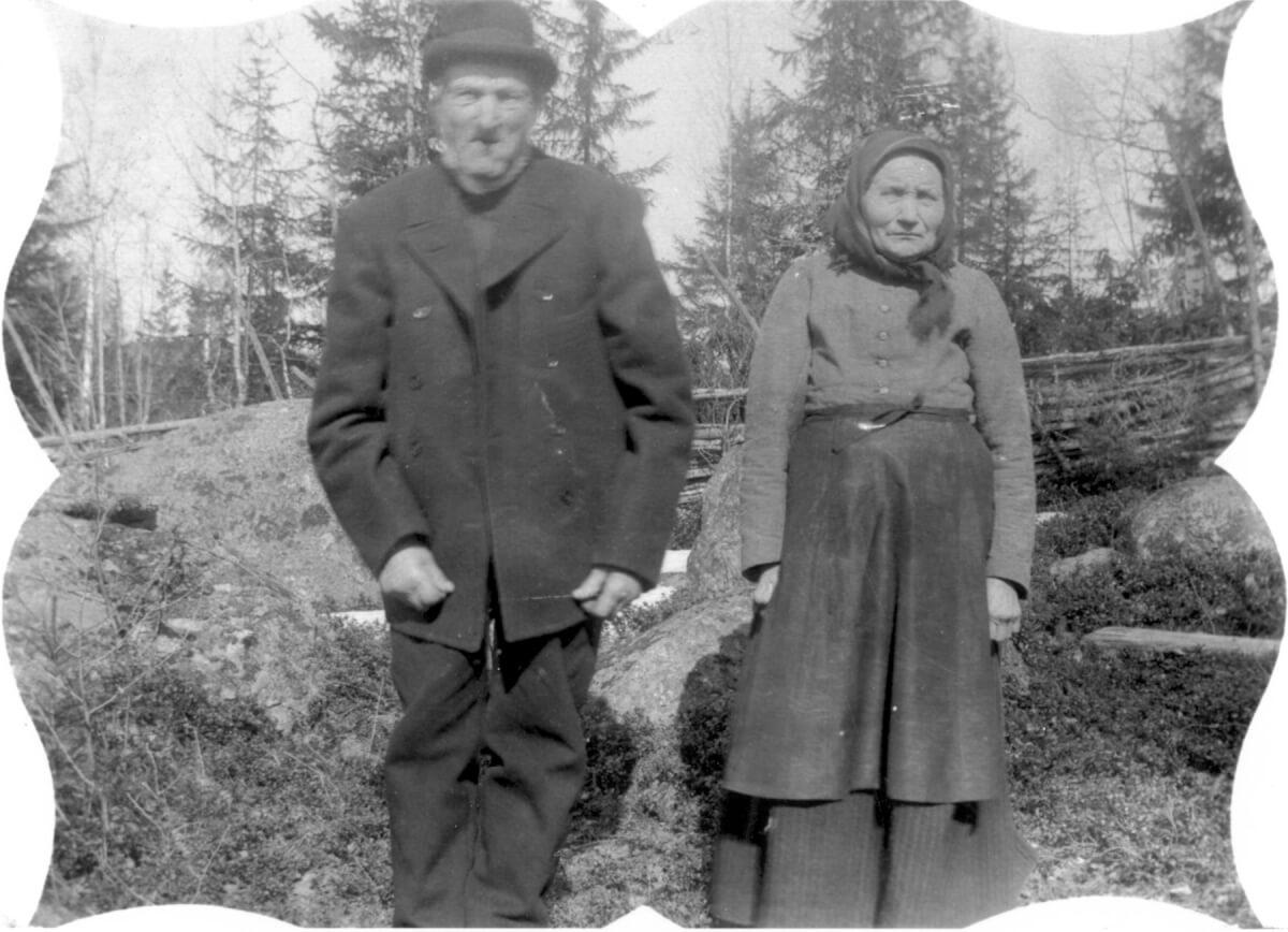 Man och hustru poserar utomhus framför en gärdesgård.