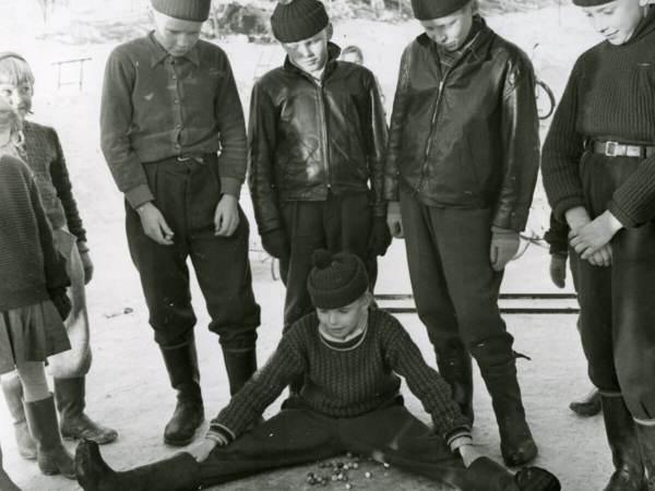 En grupp barn spelar kula. En pojke sitter ned och ramar in kulorna med sina ben.