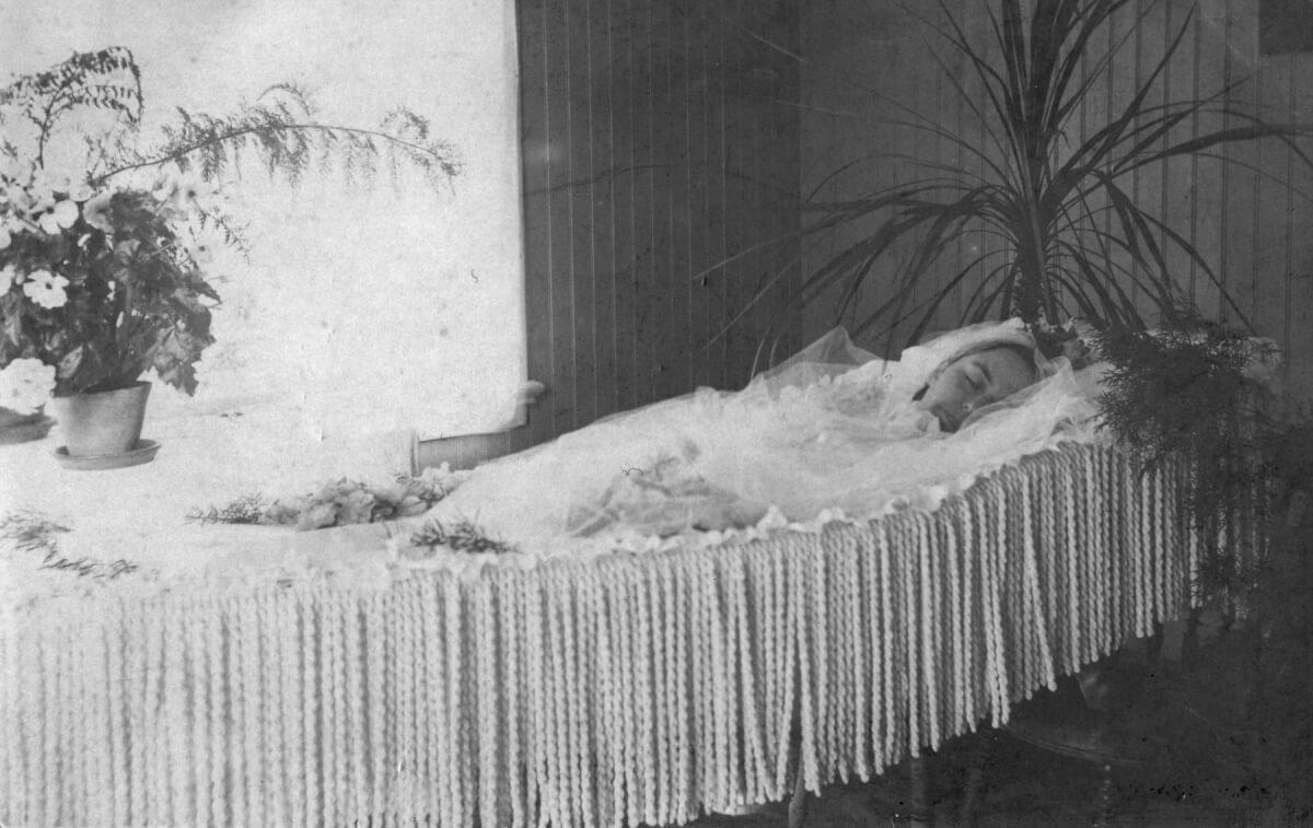 En kvinna ligger i sin kista under en likvaka.