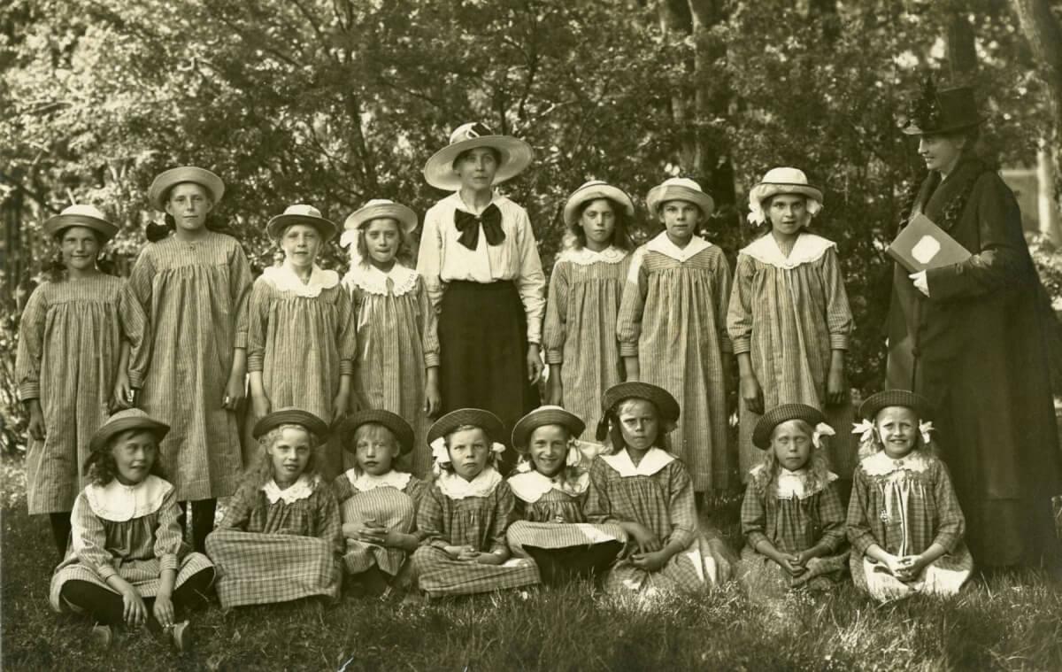 Ett gruppporträtt med femton flickor. Ena raden står uppställda, den andra raden sitter framför dem. Ett grönskande träd bildar bakgrund. Två kvinnor syns, en svartklädd kvinna står längst till höger och en kvinna i svart kjol och vit blus med en stor rosett står i mitten. Flickorna har stråhattar och är ungefär 7 – 10 år gamla. Tiden är ungefär 1910-1915.