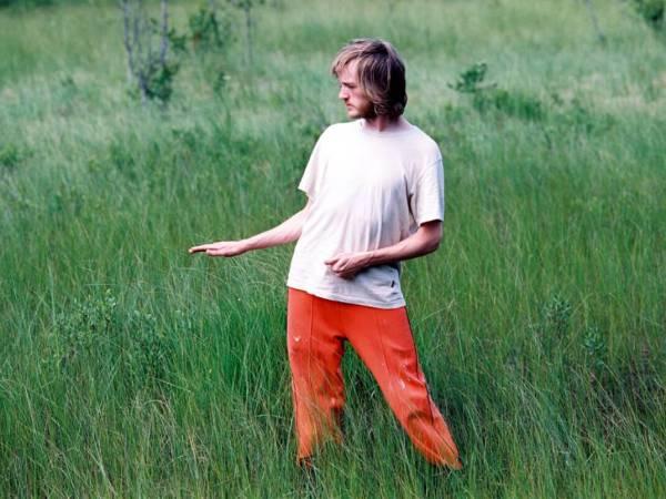 En man iförd orangea byxor och vit t-shirt står i gräset.