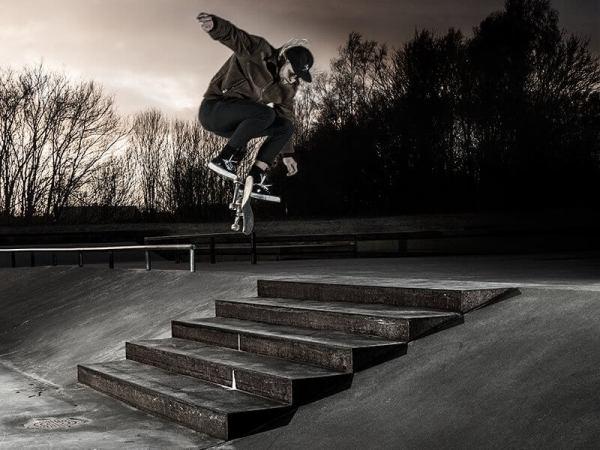 En skateboardåkare som hoppar över trappa utomhus.
