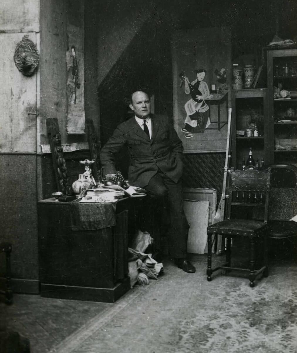 Porträtt av konstnären John Sten i inomhusmiljö. Han sitter lutad mot skrivbordet.