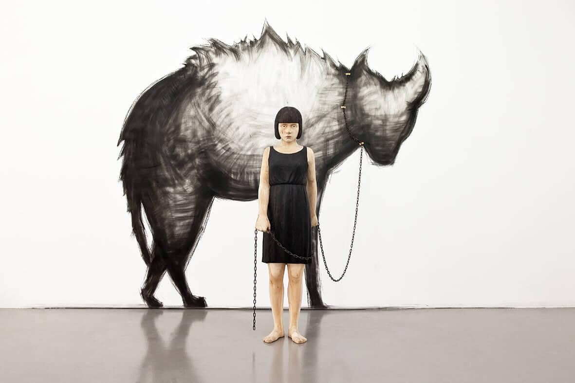 En träskulptur föreställande en kvinna ståendes framför en vägg och hållandes en kedja. Kedjan är fäst vid en hyena som är målad på väggen bakom kvinnan.