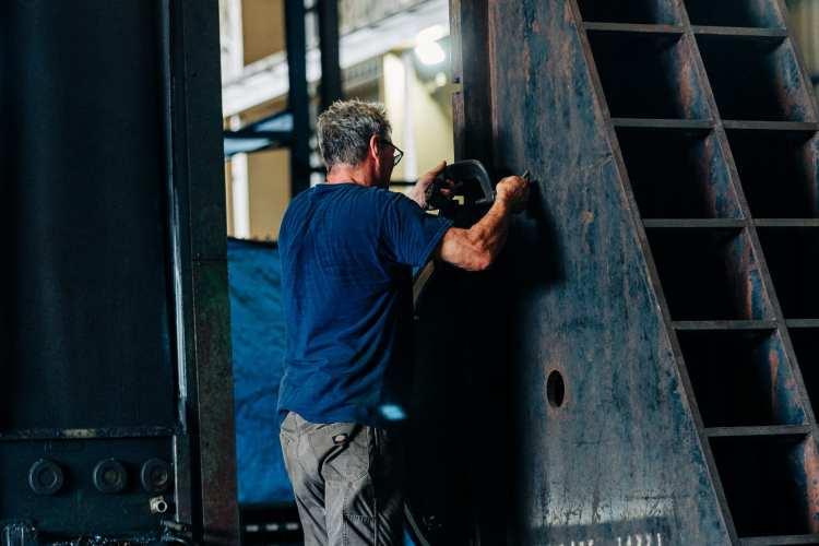 Man tightening clamp around steel piece for machining