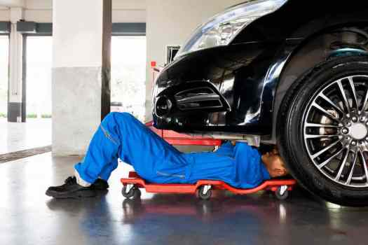 Mechanic in blue uniform lying down and working under car service garage